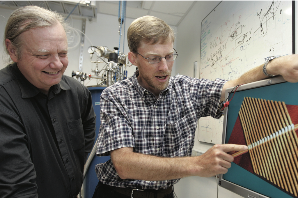 The picture shows two scientists at HP Labs in Palo Alto, California. They observe a one-dimensional array of 17 memristors based on titanium oxide.